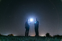 hallow of light around two men holding a shining flashlight