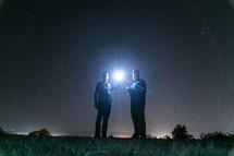 hallow of light around two men holding a shining flashlight