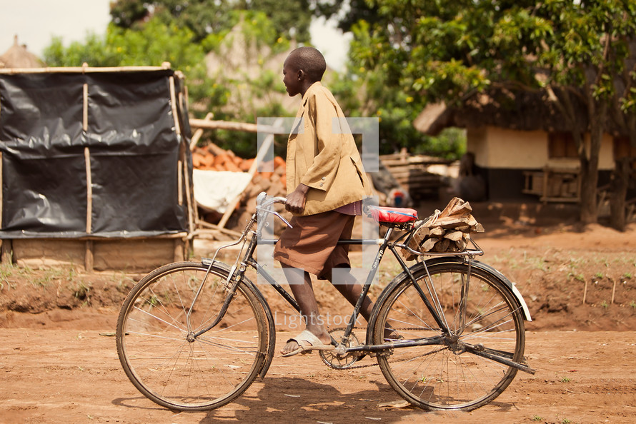man riding a bike on a dirt road