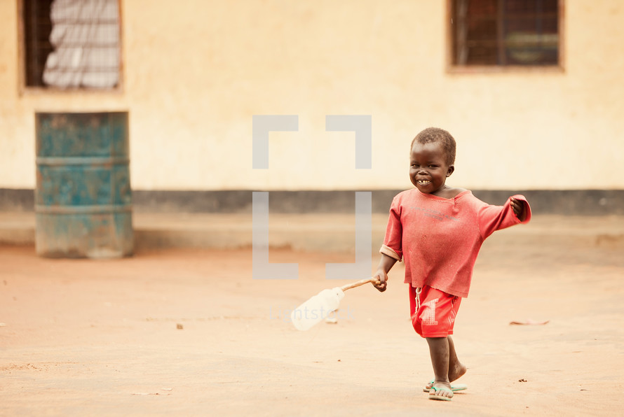 Boy playing with a bottle on a stick.