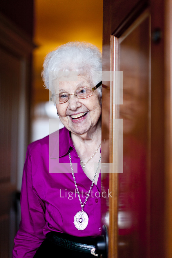 woman smiling from behind a door