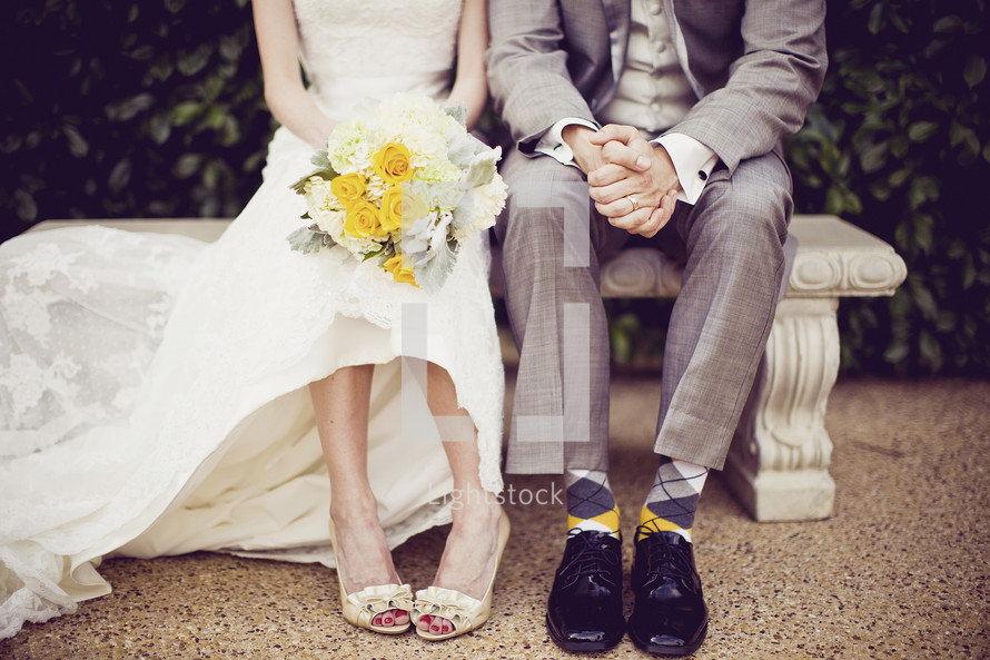 A bride and groom sit on a bench after their wedding