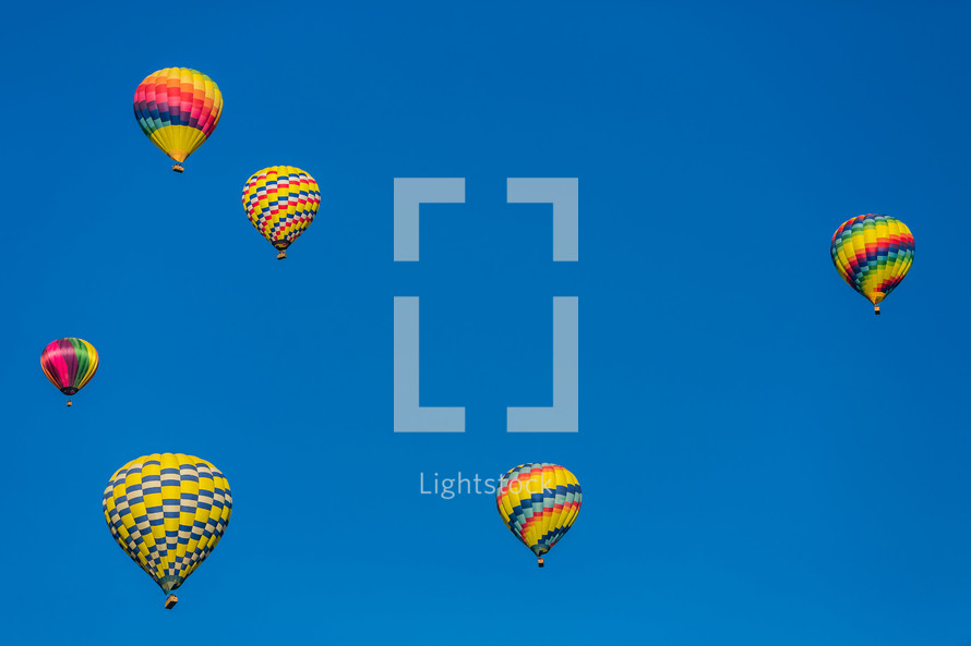 Hot air balloons in a blue sky.