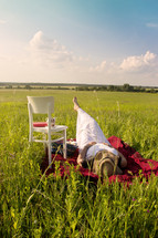 a woman relaxing lying on a blanket in the grass