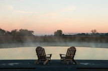 adirondack chairs on a dock at sunrise
