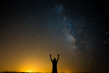 silhouette with raised hands under stars in the night sky