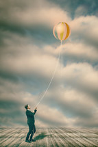 a man hanging onto a balloon