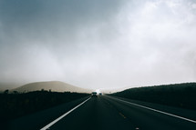 a car traveling down a road in the morning