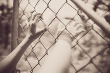 hands grasping to a chain link fence