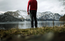 Man standing in the grass at the edge of a lake, overlooking a snow-covered mountain range.