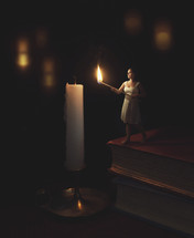 tiny woman lighting a candle
