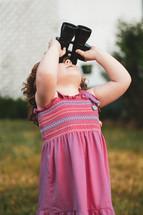 a girl looking through binoculars