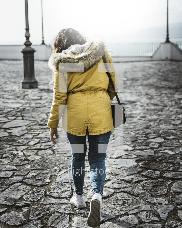 a woman in a coat walking across stone pavers