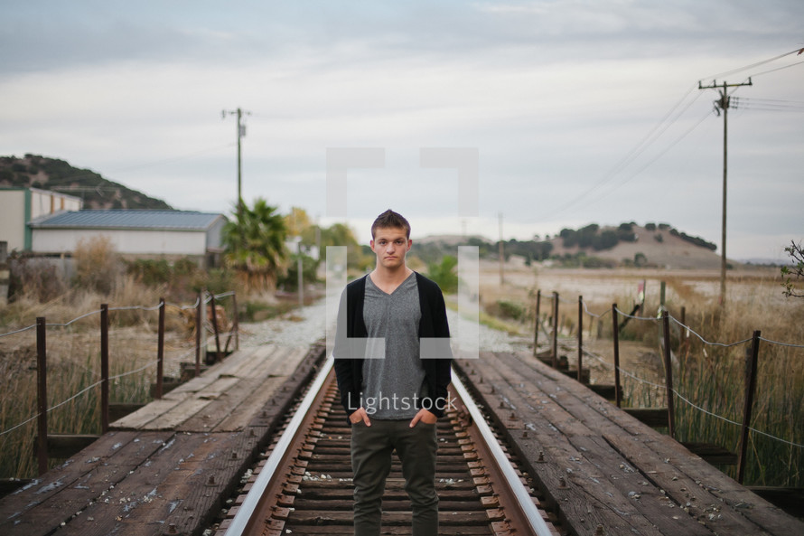 young man with hands in his pockets standing on railroad tracks