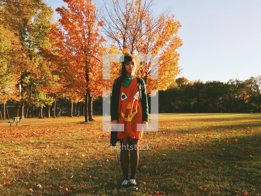 Girl in a pumpkin costume standing outside with fall foliage.