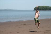 teen boy jumping for joy on a beach
