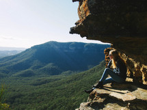 woman sitting on the edge of a mountain