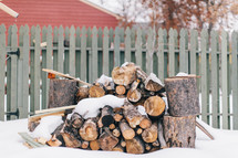 snow and axes near stack of firewood