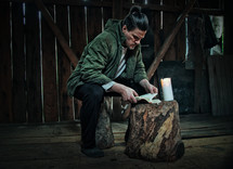 man reading a Bible in a barn by candlelight