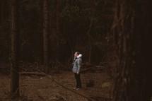 Man standing in the dark woods.