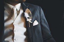 Feather boutonniere on a suit lapel.