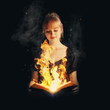 Girl holding an open Bible with flames emerging from the center of the pages.