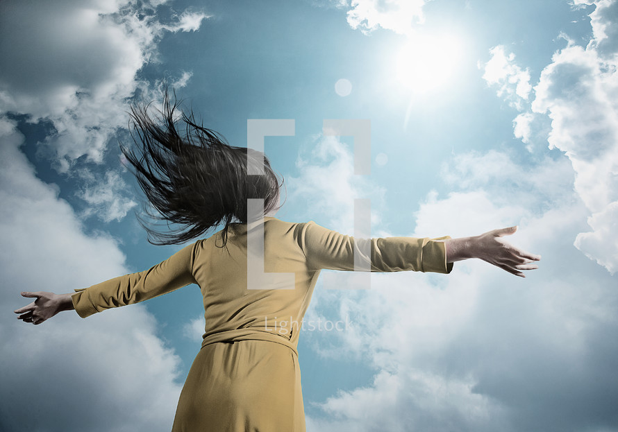 a woman with open arms standing under a blue cloudy sky