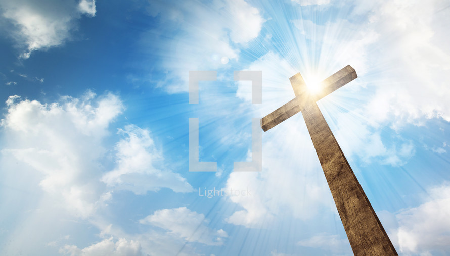 A wooden cross with bright sun and clouds in the background.