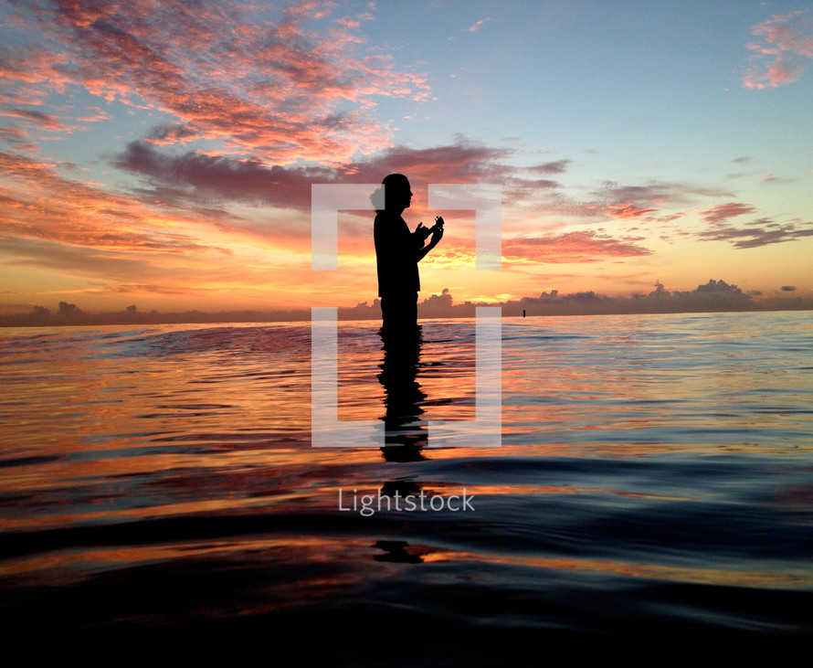 silhouette of a woman standing in water at sunset