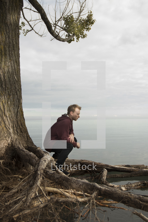 a man sitting on a tree roots looking out at the ocean