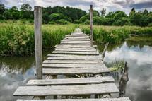 old weathered and broken foot bridge across water