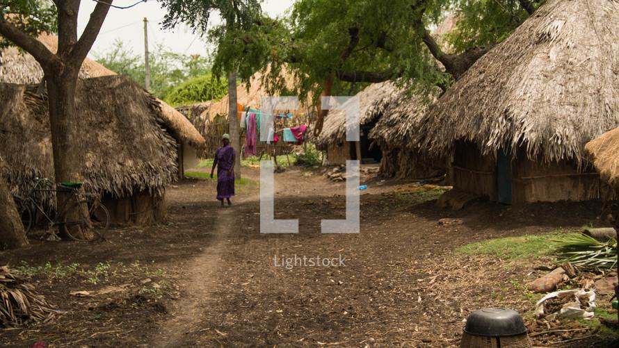 a woman walking through a village