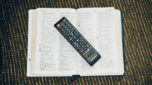 remote control on the pages of a Bible