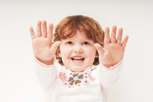 a toddler with her hands up
