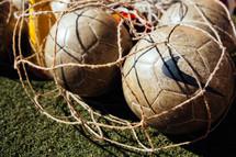 soccer balls in a a net bag