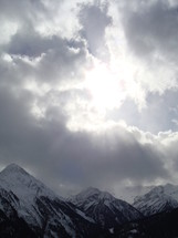 Sun breaking through in a wintry mountain scene,