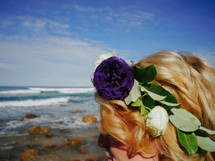 flowers in a girls hair at the ocean