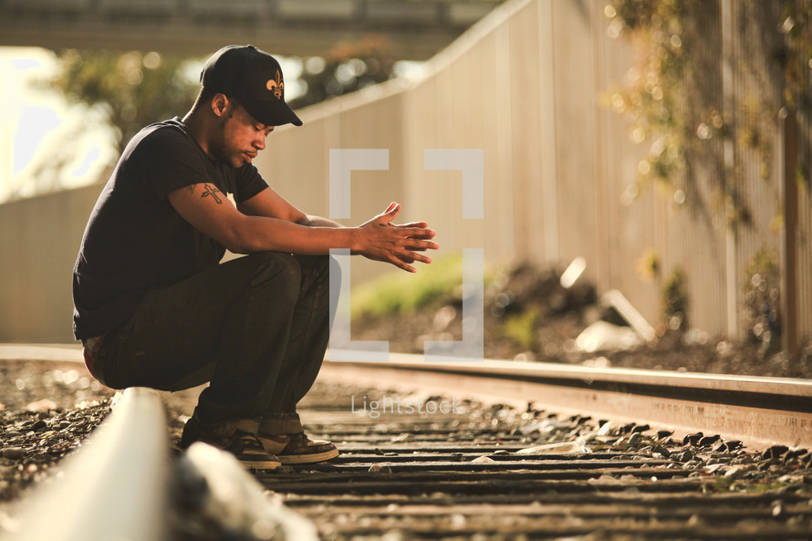 Man sitting on railroad tracks with head bowed