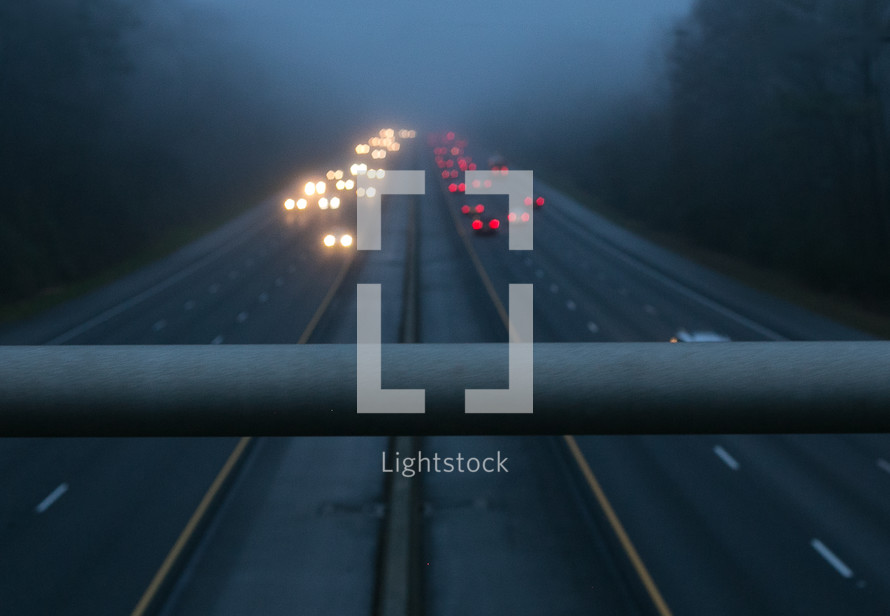 looking down at traffic in fog from a bridge