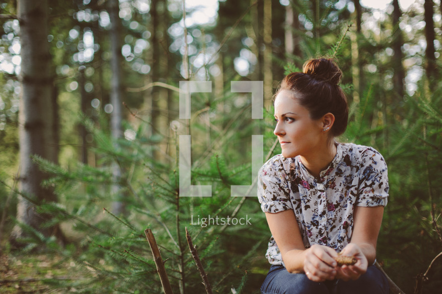 a woman sitting alone in a forest in thought