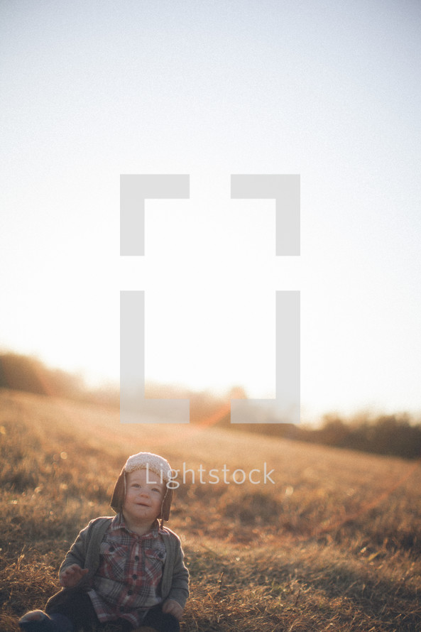 Toddler child sitting on grassy hill at sunrise.