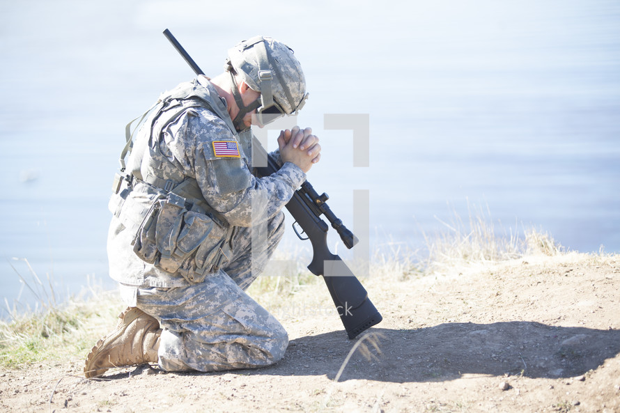 soldier with a rifle kneeling in prayer to God