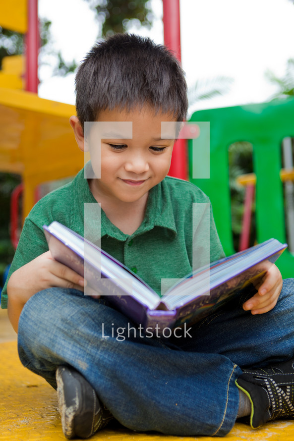 An Asian boy reading a book on a playground