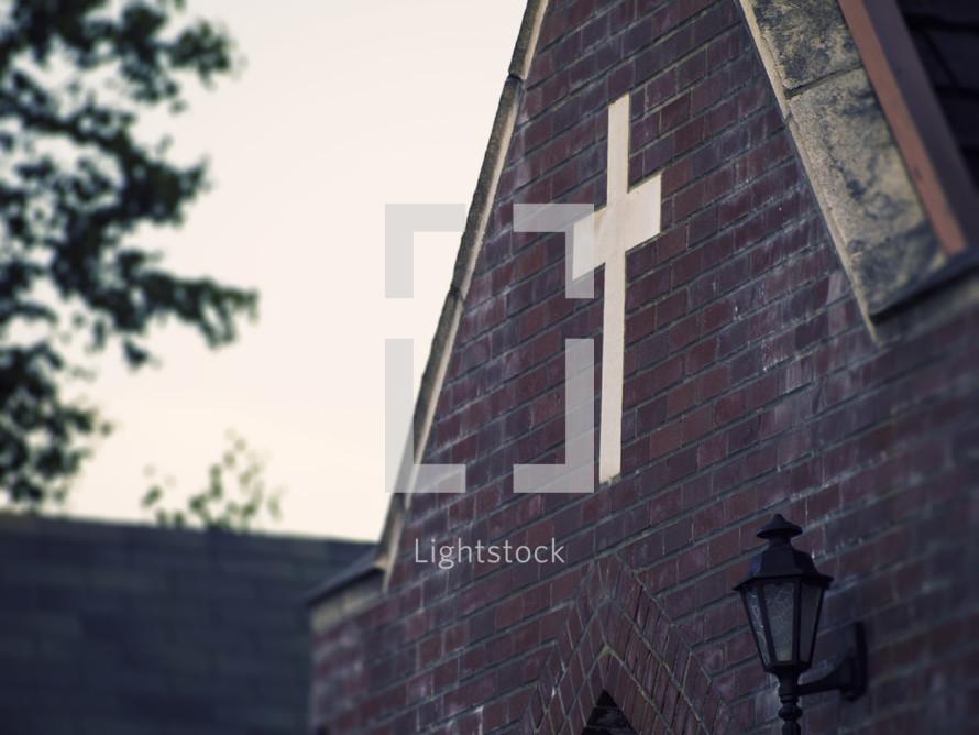 A cross embedded in a brick church wall.