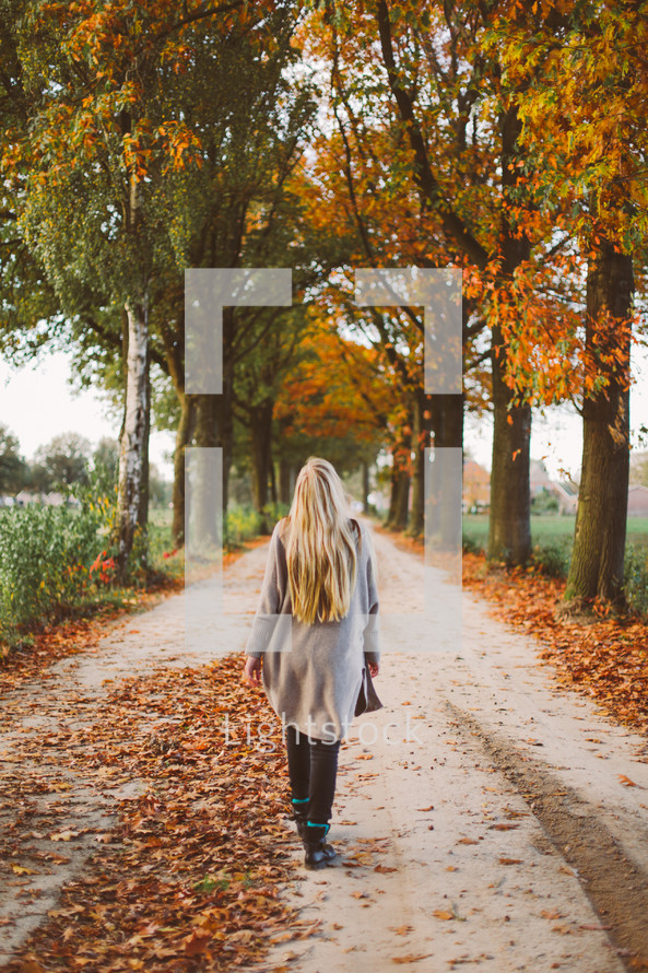 woman walking down a rural dirt road covered in fall leaves