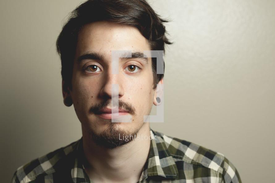 mans face with ear gauges
