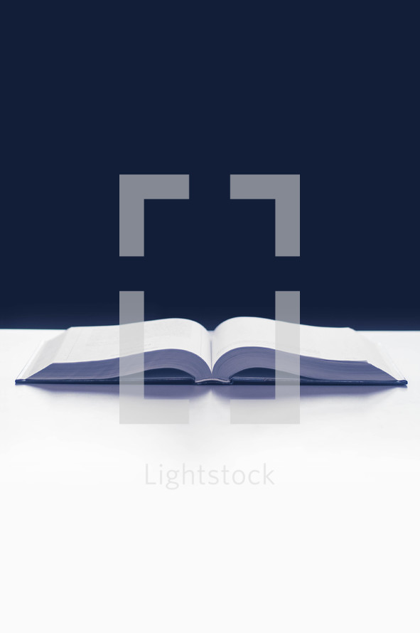 open Bible on a white table again a black background