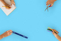 students with school supplies on a blue table top.
