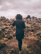 a woman hiking up a rugged mountainside