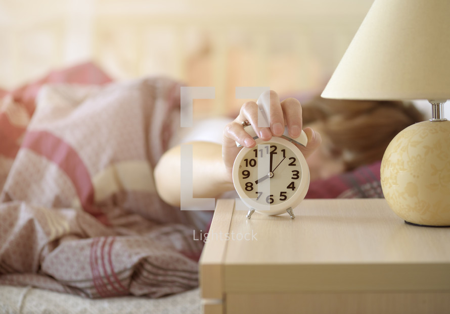 woman in bed turing off her alarm clock